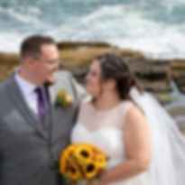 Smiling bride holding bouquet of sunflowers facing groom who has arm around her rocky ocean in background at Two Lights state park in Portland Maine wedding