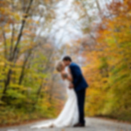 Bride leaning back pulling groom in close for a kiss on abandoned new england road with beautiful yellow and orange fall foliage surrounding