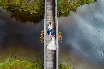 aerial drone photograhy bride and groom on bridge between islands in new hampshire white mountains