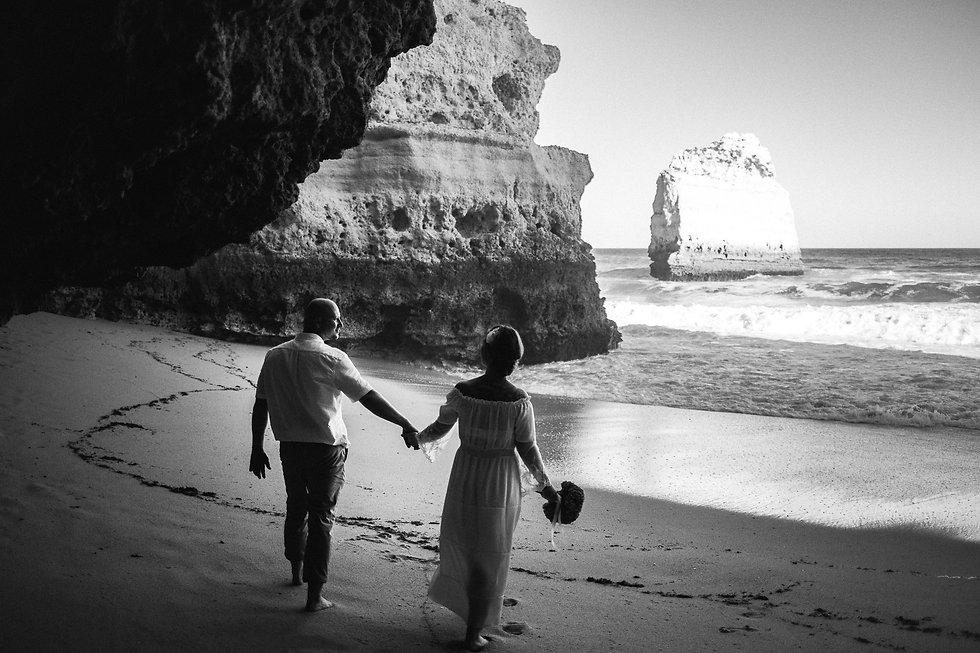 Brautpaar spaziert während der Hochzeit am Strand Praia da Marinha in Portugal an der Algarve