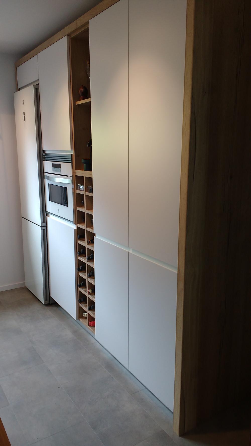 Zona columna, con electrodomésticos en color blanco y una zona botellero
