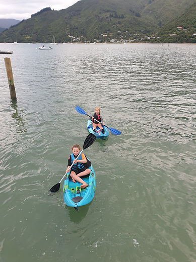 Two kids kayaking in the ocean in the Marlborough Sounds
