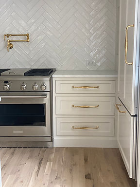 White kitchen cabinets with unlacquered brass hardware