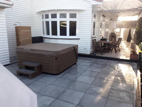 New paved courtyard with outdoor shower, spa and garden borders