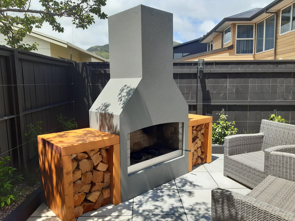 Outdoor fire and crafted macrocarpa woodboxes on paving