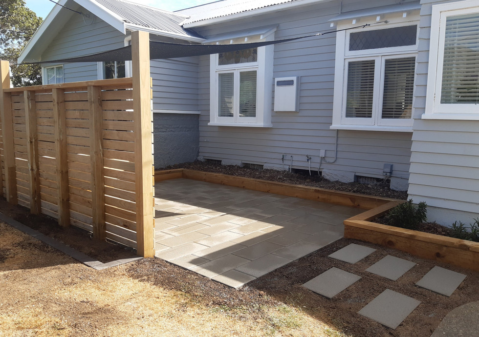 Paved patio with garden borders, screen and shadesail