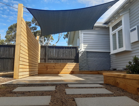 Paved patio with planter, garden borders, screen and shadesail