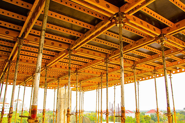 building-construction-site-with-orange-steel-girder-trusses-beams-and-black-composite-shoring-boards-support-next-floor-pour