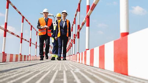 2-men-and-1-woman-engineers-wearing-orange-safety-vests-and-helmets-walking-across-red-and-white-industrial-footbridge