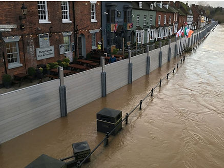 removable-reusable-modular-flood-barrier-wall-system-protects-homes-and-restaurants-and-couple-walking-along-flooding-river