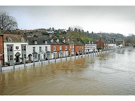 modular-flood-barrier-wall-system-protects-riverside-raw-of-old-houses-from-flooding-river-with-background-of-hillside-city