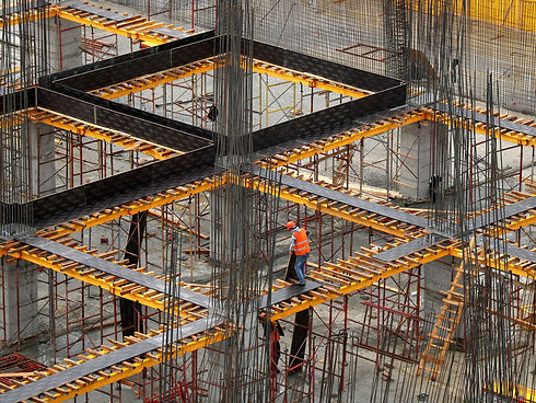 worker-in-orange-safety-on-construction-site-concrete-slab-steel-rebar-mesh-with-black-composite-walkways-and-shoring-boards