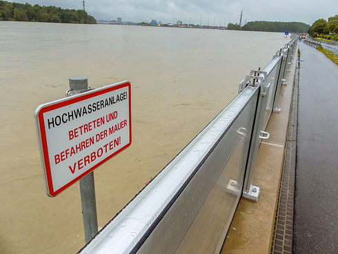 modular-removable-flood-barrier-wall-system-with-red-and-black-warning-sign-protects-riverside-promenade-from-flood-water