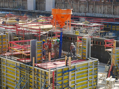 Construction-worksite-with-4-workers-in-helmets-pouring-concrete-into-formwork-system-from-orange-concrete-pouring-bucket
