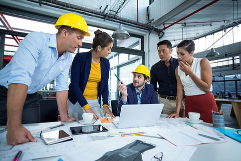 team-of-five-engineers-with-two-yellow-safety-helmets-meeting-in-office-by-desk-with-laptop-and-tablets