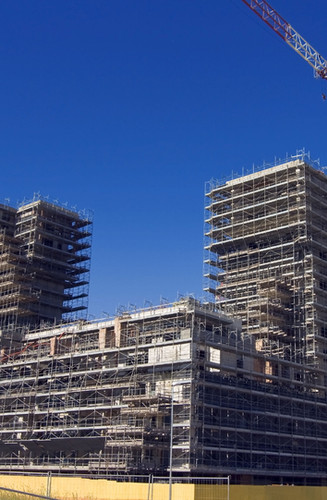 construction-site-of-large-building-with-two-residential-towers-covered-in-scaffolding-and-flanked-by-two-large-cranes