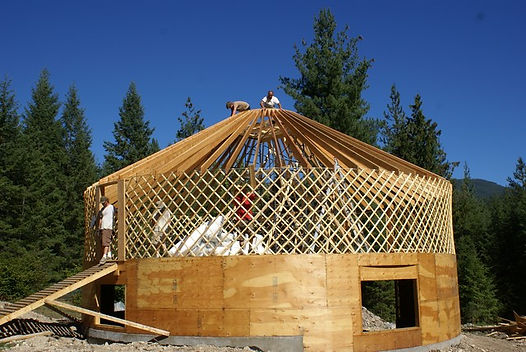 nomad shelter alaskan yurt construction with open lattice and rafters in the forest