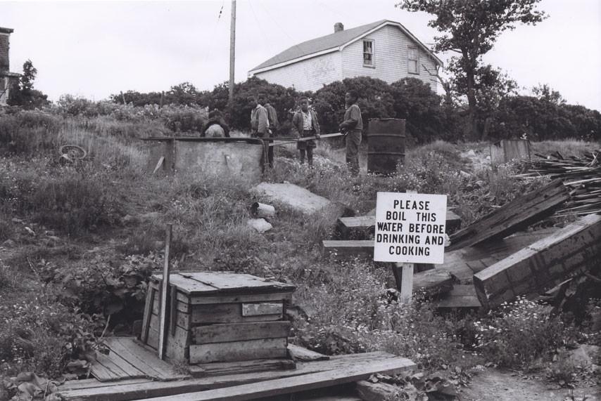 Children playing around water well, Africville, Nova Scotia, 1965.