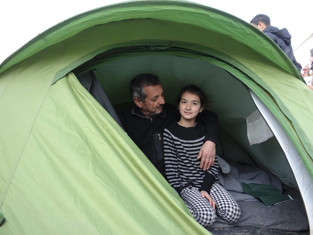 A Syrian Refugee child names RIta in Idomeni Camp. Here she is seen in a tent with her father.