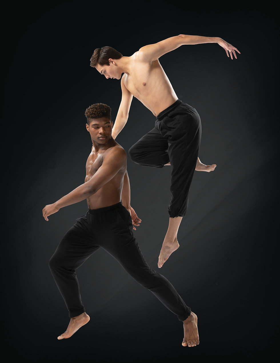 Two male dancers wearing black pants paused during a dance routine.