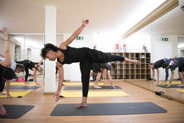 Yoga pose from an instructor in a white room