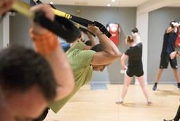 Man using TRX ropes in a gym class