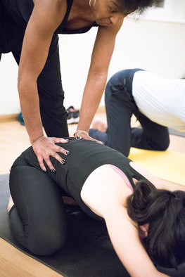 instructor pushing on lower back in a yoga class