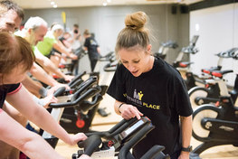 gym instructor checking a spin bike