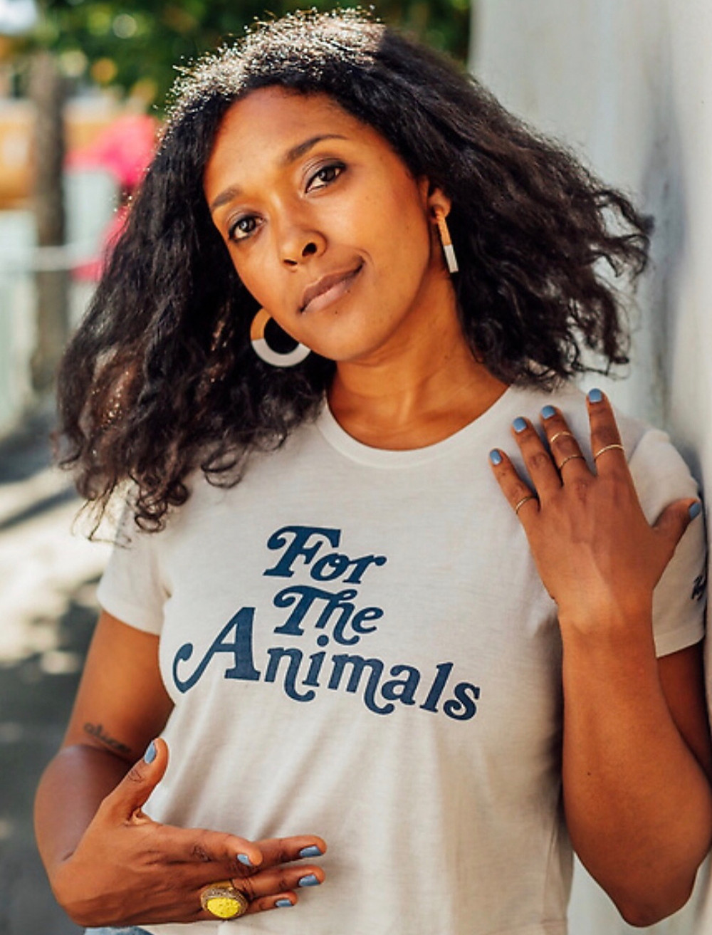 Portrait photo of Yvette, who is looking into the camera with her head slightly tilted to the side. She is wearing a t-shirt that reads 'For the Animals'