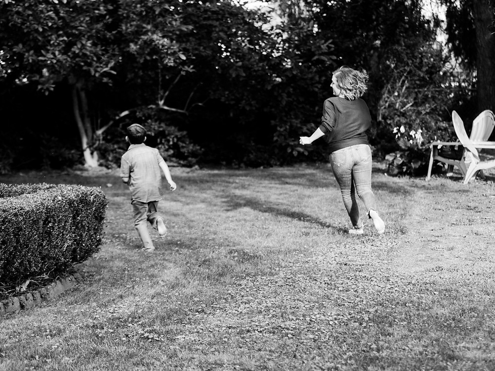 Candid family photo of a mother and son running in their back yard in Bridgeville, Pa by LeeAnn Stromyer