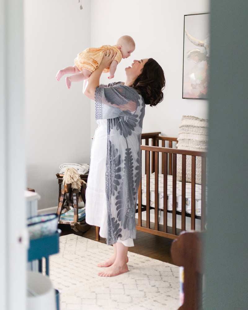 Portrait of a Mom holding her baby in the air while standing in the nursery by LeeAnn K Photography