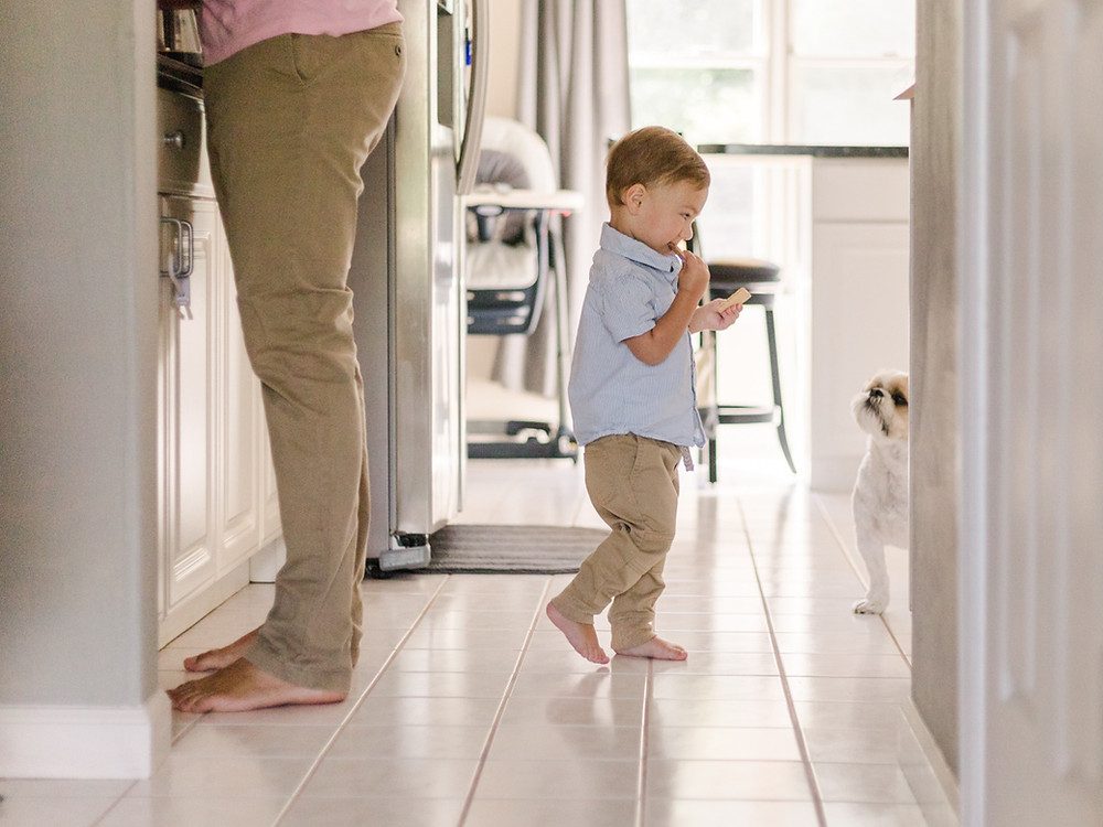 In-home lifestyle family photo of a boy eating crackers walking away from his dad by LeeAnn Stromyer.