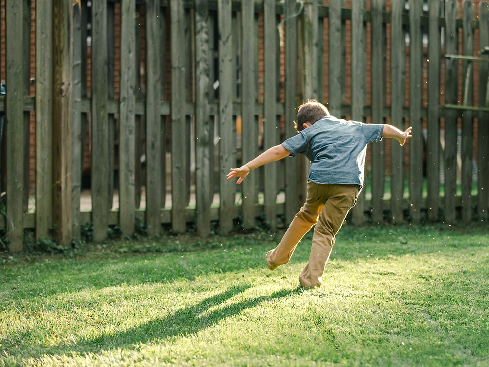 Portrait of a boy running in his backyard bare foot as the sun is shining around him by LeeAnn K Photography