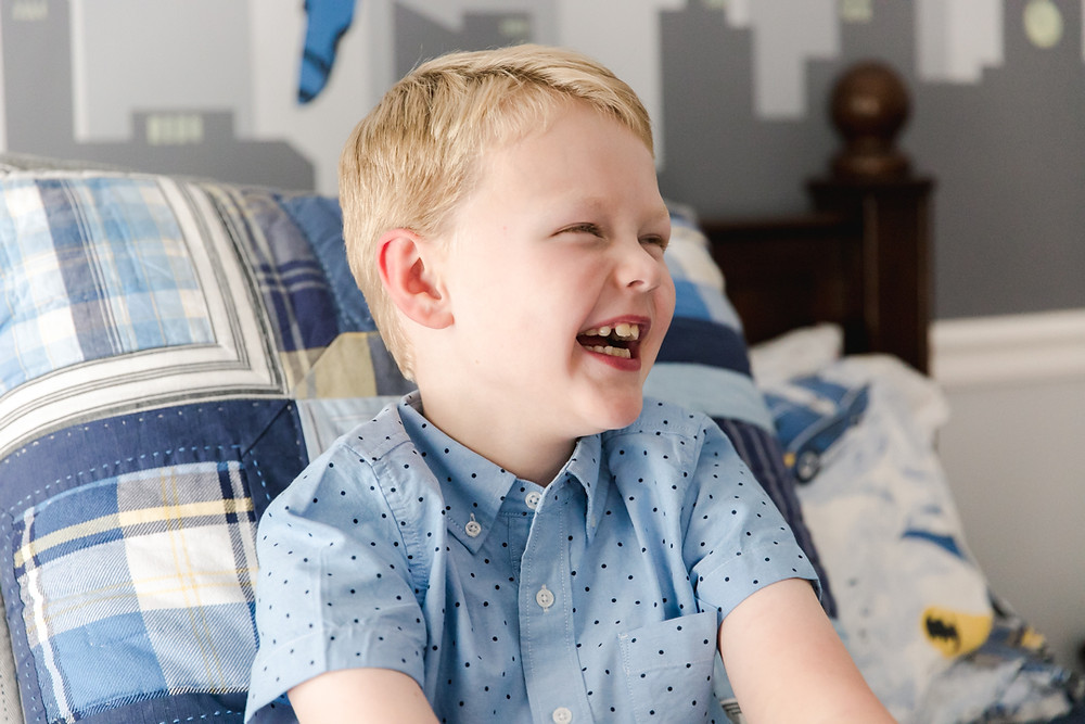 Candid family photo of a boy laughing by LeeAnn Stromyer