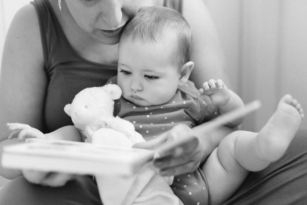 Portrait of an 8-month old with her mom reading a book  for an in-home family session in Pittsburgh, Pa  by LeeAnn K Photography