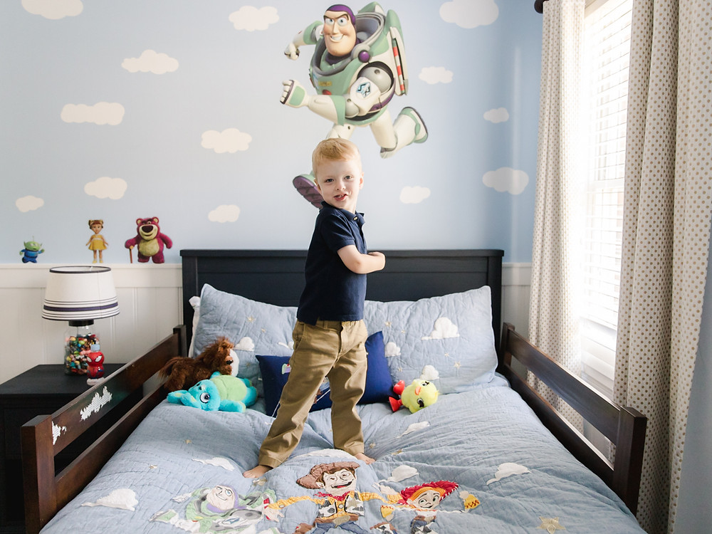 Portrait of a toddler in his bedroom imitating Buzz Light year from Toy Story by LeeAnn  K Photography