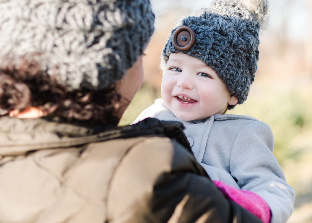Photo of a one-year old smiling at the camera near Christmas trees for holiday mini-sessions by LeeAnn Stromyer
