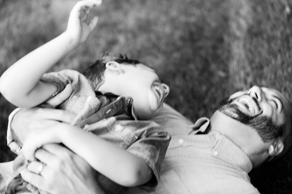 Black and white portrait of a father and his son laughing laying in their yard by LeeAnn Stromyer a Pittsburgh photographer.