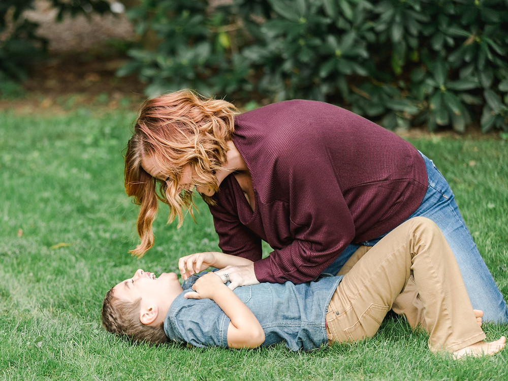 Portrait of a mom tickling her son in their backyard by LeeAnn Stromyer.