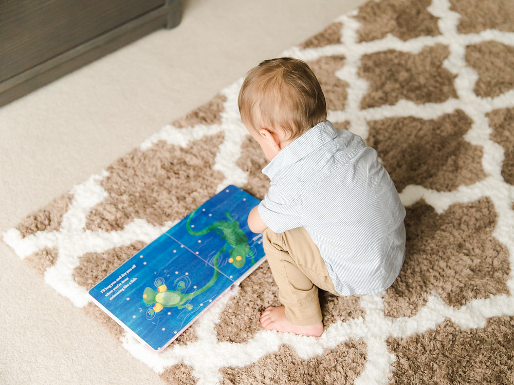 Documentary style portrait of toddler reading a book by LeeAnn K Photography