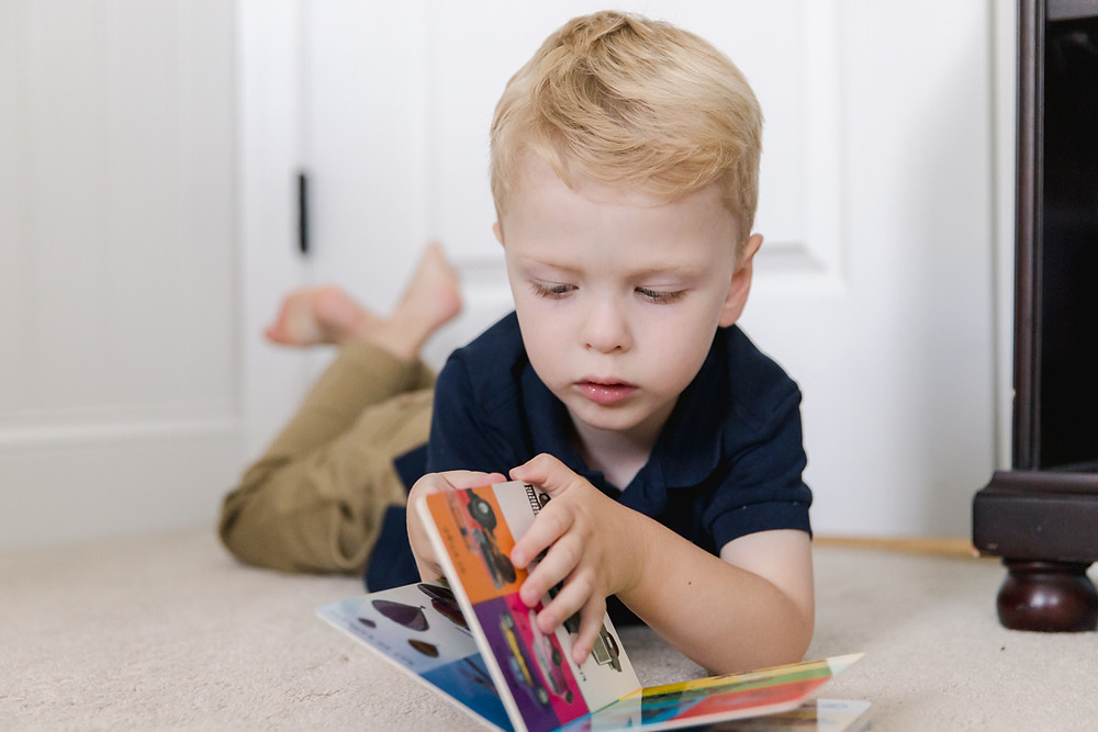 Candid photo of a toddler reading a book by LeeAnn K Photography