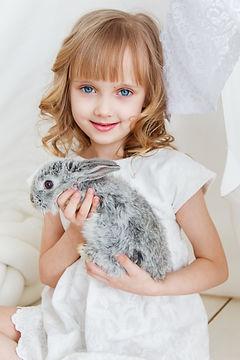 smiling-girl-holding-gray-rabbit-1462636
