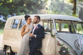 Couple drinking champagne with wedding Kombi