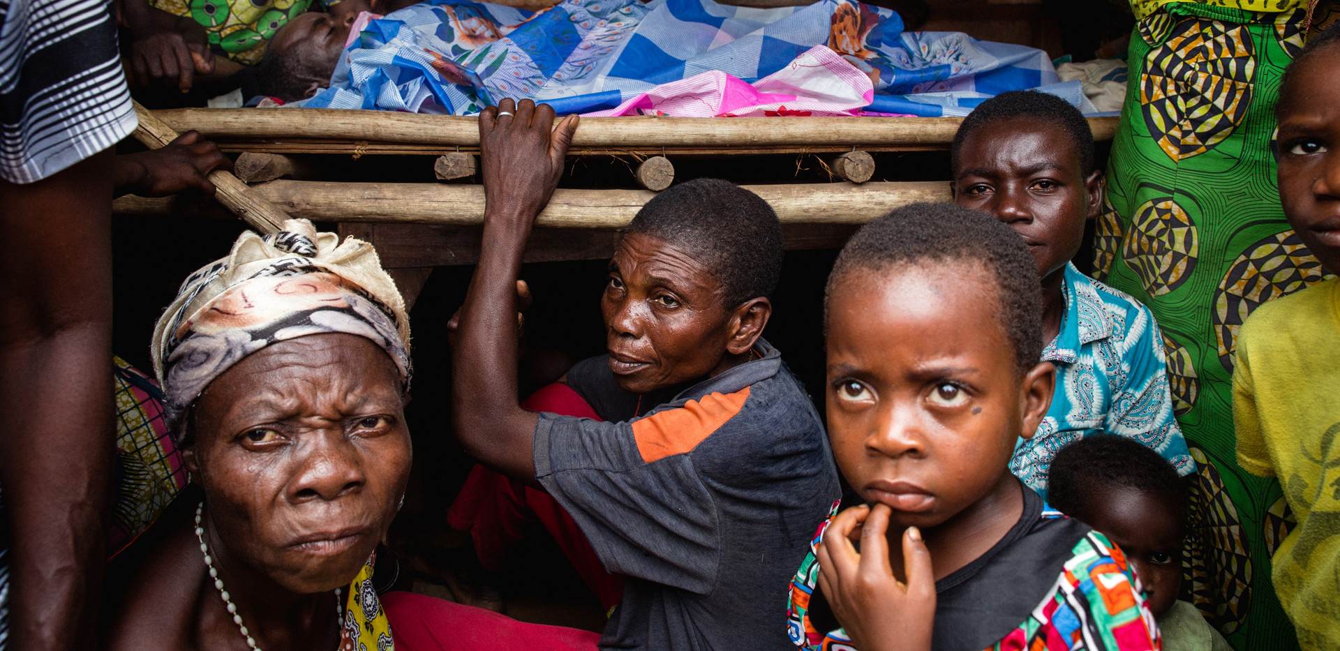In Lwemba, during a funeral, a woman mourns her husband surrounded by people from the village.