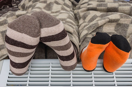 adult and child in a blanket warming feet on a heater with socks on