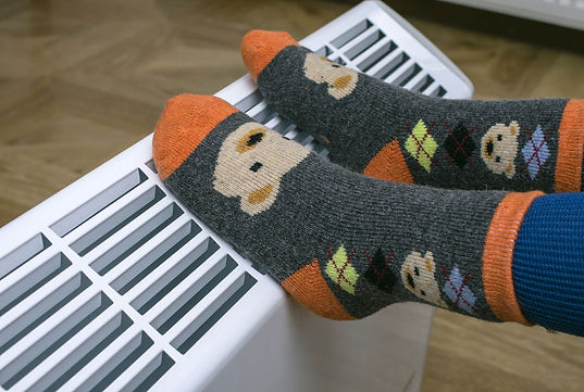 Childs feet in socks resting on a heater