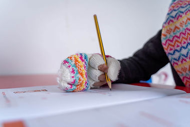 Child wearing mittens, holding pencil doing homework