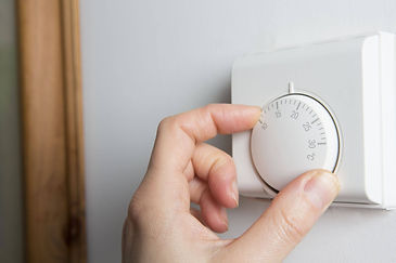 Hand turning down heating on the thermostat