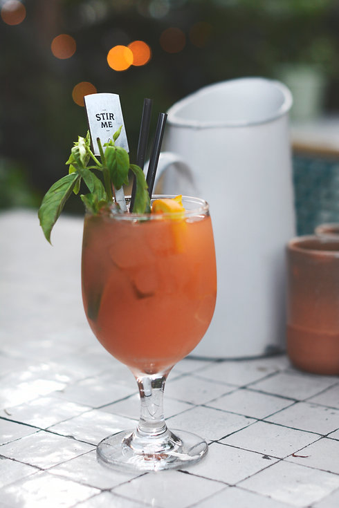 Cocktail in a glass garnished with orange and mint