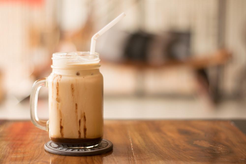 Frappuccino dans une jarre en verre transparente avec une paille et du caramel